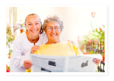 aged woman reading newspaper with her caretaker